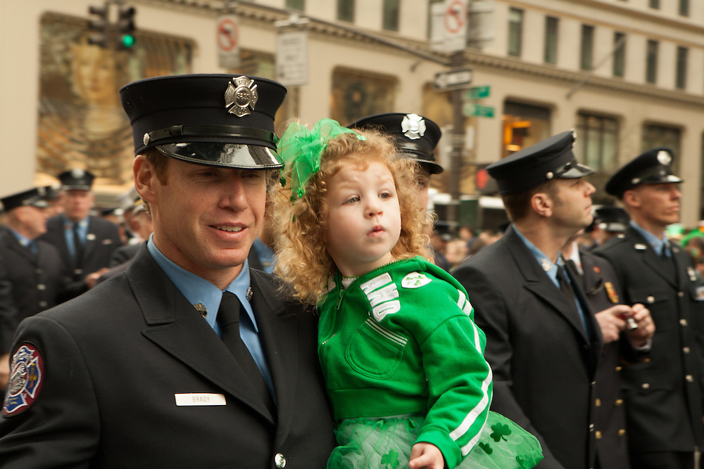 A New York firefighter carries his daughter.