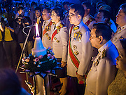 YINGLUCK SHINAWATRA (center) the Prime Minister of Thailand, reads a proclamation honoring the King while her husband, ANUSORN AMORNCHAT, stands next to her at the celebration of the birthday of the King in Bangkok. Thais observed the 86th birthday of Bhumibol Adulyadej, the King of Thailand, their revered King on Thursday. They held candlelight services throughout the country. The political protests that have gripped Bangkok were on hold for the day, although protestors did hold their own observances of the holiday. Thousands of people attended the government celebration of the day on Sanam Luang, the large public space next to the Grand Palace in Bangkok.
