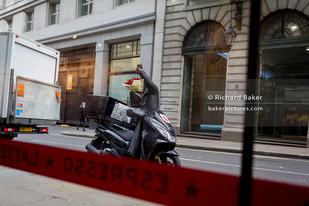 WHile holding tight to his phone, a scooter courier stretches his arm up to place a bouquet of red Valentines Day roses into a carrying container, on Threadneedle Street in the City of London, the capital's financial district, on 14th February 2020, in London, England.