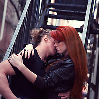 Edgy couple snuggling on stairs in an alley