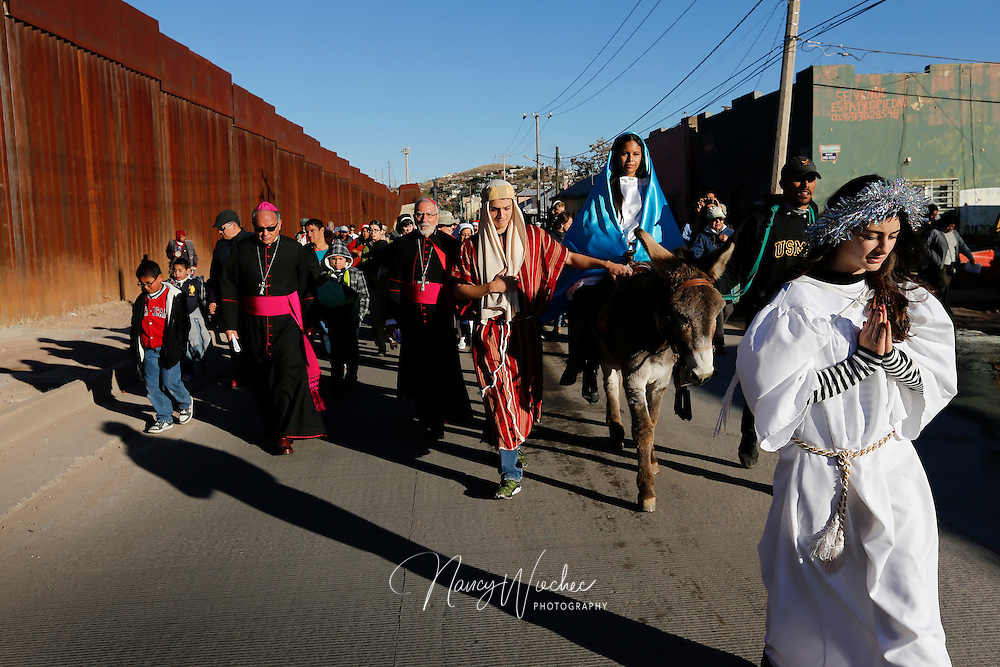 "People from the U.S. and Mexico make their way along the international border fence during a ""posada,"" the commemoration of Mary and Joseph's search for shelter, Dec. 20 in Nogales, Sonora. The annual Nogales event held by the Kino Border Initiative and Dioceses Without Borders reflected on the struggles of migrants and migrant families. Bishops Jose Leopoldo Gonzalez Gonzalez of Nogales, Sonora, and Gerald F. Kicanas of Tucson, Arizona, are pictured at left. (CNS photo/Nancy Wiechec)(CNS photo/Nancy Wiechec)"