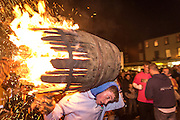 A young tar barrel runner hold a burning barrel shoulder high through the narrow streets of Ottery St Marys.