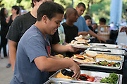 Kelvin Davilla, 13, of Rochester, serves himself a burger at Frontier Field in Rochester on Friday, July 31, 2015. Students from School #17 ate dinner at the stadium, and then camped on the field Friday night.