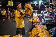 19 OCTOBER 2012 - BANGKOK, THAILAND:   A flower vendor sets up his marigold display in the Bangkok Flower Market. The Bangkok Flower Market (Pak Klong Talad) is the biggest wholesale and retail fresh flower market in Bangkok.  The market is busiest between 3:30AM and 6AM.     PHOTO BY JACK KURTZ
