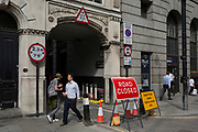 Pedestrians walk past a Road Closed sign at the entrance of Austin Friars in Threadneedle Street in the City of London - the capital's financial district, on 3rd September 2018, in London England. Austin Friars, London was an Augustinian friary in the City of London from its foundation, probably in the 1260s, until its dissolution in November 1538. It covered an area of about 5.5 acres (2.2 hectares) a short distance to the north-east of the modern Bank of England and had a resident population of about 60 friars. Nowadays the site is mainly occupied by office blocks.