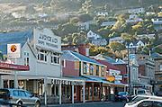 Cold and hazy morning sunlight illuminates trees and houses overlooking heritage shops and bars on London Street, Lyttelton, New Zealand