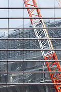 An office building window reflects a crane and scaffolding  at the construction site for the new main stadium for the 2020 Tokyo Olympics in Gaiemmae, Tokyo, Japan Tuesday June 26th 2018. After many delays the main stadium construction is expected to be finished by November 2019. The Tokyo 2020 Olympics will take place from July 24th to August 9th  2020