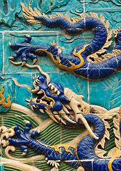 Detail of ceramic tiled dragon on historic Nine Dragon Wall in Beihai Park in Beijing China