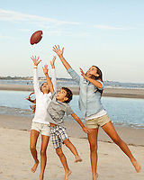 Three siblings jump in the air trying to catch a football while playing on the beach.