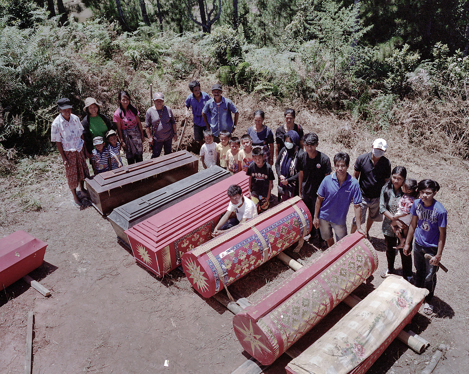 Family members pose for a portrait next to coffins containing dead relatives before putting them back in the tomb.<br />
