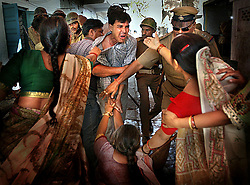 Indian police drag away a man believed to be instigating violence in central Ahmedabad, India, March 3, 2002.  The violence left more than a thousand dead and an entire nation traumatized and divided.
