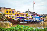 Traditional boat moored on Thu Bon river in front of Hoi An's old buildings, Vietnam, Southeast Asia