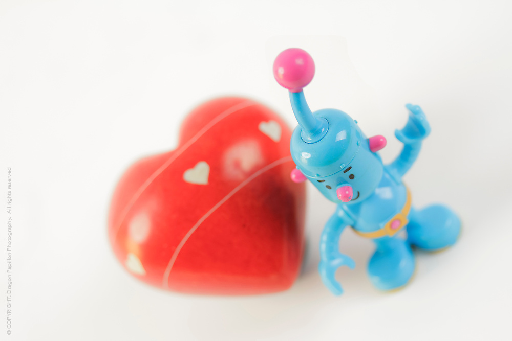little blue robot with big red heart on white background