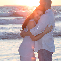 Couple embraces by ocean waves flare