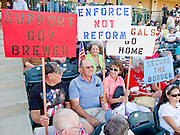 """May 29 - TEMPE, AZ: Opponents of illegal immigration and supporters of Arizona SB070 at a rally in Tempe, AZ. About 3,000 people attended a """"Buy Cott Arizona"""" rally at Tempe Diablo Stadium in Tempe, AZ Saturday night. The rally was organized by members of the Arizona Tea Party movement to show support for Arizona law SB1070. The """"Buy Cott"""" is a reaction to the economic boycott planned by opponents of SB1070. SB1070 makes it an Arizona state crime to be in the US illegally and requires that immigrants carry papers with them at all times and present to law enforcement when asked to. Critics of the law say it will lead to racial profiling, harassment of Hispanics and usurps the federal role in immigration enforcement. Supporters of the law say it merely brings Arizona law into line with existing federal laws.  Photo by Jack Kurtz"""