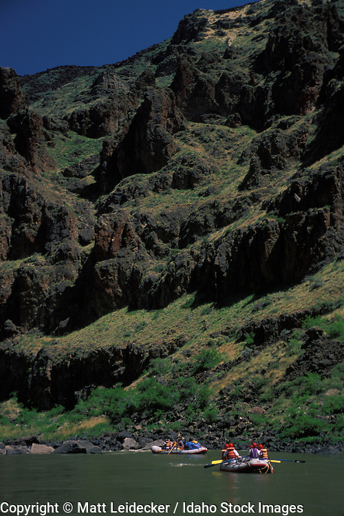 Idaho, Owyhee, Canyonlands,  river.  Rafters in calm water. View of cliff wall.