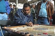 The 2003 Carrom Association International Championship winner Shaheen Miah plays a strike during an early qualifying round at Spitalfield's Market, London.