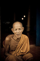 A monk with a kind smile rests in front of a wat in the village of Muang Ngoi in northern Laos, Southeast Asia.
