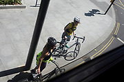 Two women cyclists wait at the kerb for a London bus to pass before crossing a corner of the Walworth Road in south London, on 13th June 2020, in London, England.