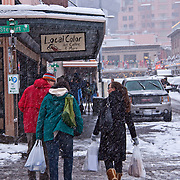 People with shopping bags walking on snow covered street, Pike Place Market, Seattle, Washington
