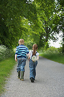 Boy and girl (5-6 7-9) walking on country lane