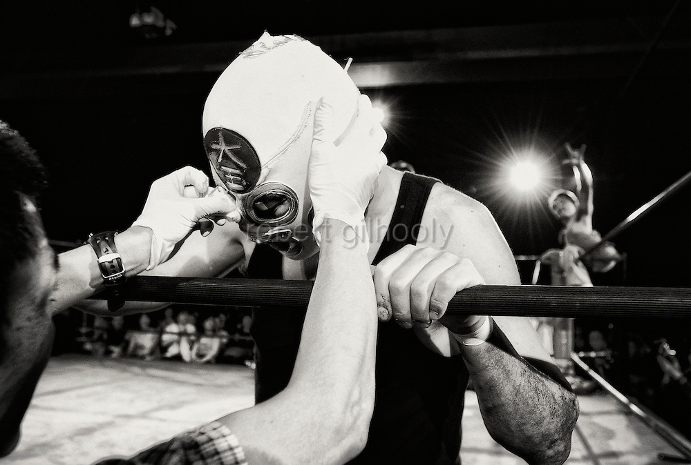 A wrestler gets some medical attention for his bloodied face while his opponent gestures while sitting on the ropes  in a bout  at Doglegs, an event for wrestlers with physical and mental challenges in Tokyo, Japan.