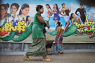 YANGON, MYANMAR - SEPTEMBER 23, 2012.Women wearing traditional longyi walk in front of a modern movie billboard in Yangon, Myanmar on Sep 23, 2012..After nearly five decades where the military had tight control over people's lives, the arrival of democracy has led to debates about a new national identity for the country..(Photo by Kuni Takahashi)..