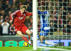 LIVERPOOL, ENGLAND - Wednesday, December 16, 2009: Liverpool's Fernando Torres rounds Wigan Athletic's Titus Bramble to score his side's second goal during the Premiership match at Anfield. This was Torres' 100th appearance for Liverpool and his 49th goal.(Photo by: David Rawcliffe/Propaganda)