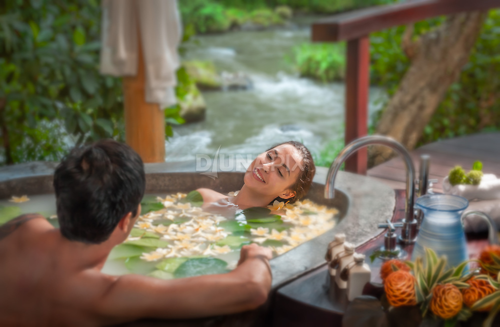 A young Asian couple enjoys a coconut milk herbal bath in a giant stone basin along the banks of the Ayung River at Fivelements Healing Center, Bali. Spa photography by Djuna Ivereigh.