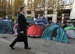 © Licensed to London News Pictures. 17/11/2011, London, UK. A business man walks past Occupy London tents outside St Paul's Cathedral today 17 November 2011.  Photo credit : Stephen Simpson/LNP