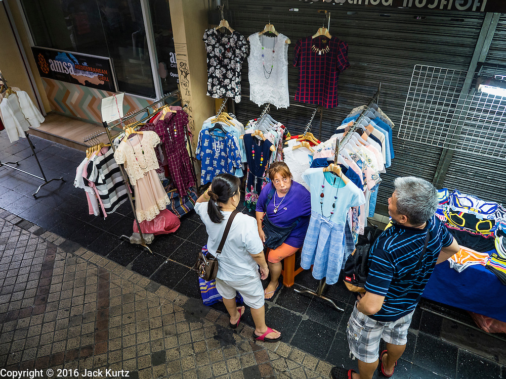 26 MAY 2016 - BANGKOK, THAILAND:  Vendors in the Silom Road night market wait for customers in their booths. The night market on Silom Road, close to Bangkok's famous Patpong tourist area, is being closed by the Bangkok municipal government. Vendors have been told they have to leave the sidewalk on Silom Road by the end of May, 2016. The market is the latest street market being shut down by city officials as a part of the government's plan to clean up Bangkok. The Silom Road night market sells mostly tourist oriented clothes, inexpensive Thai art, and bootleg movies on DVD.      PHOTO BY JACK KURTZ