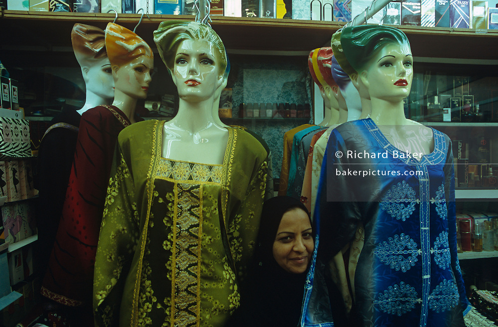 A lady wearing a Hejab sits among Western ethnic fashion mannequins in a womens' clothes shop in Manama City, Bahrain.