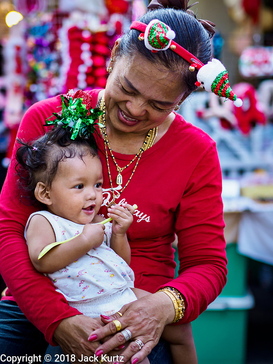 """23 DECEMBER 2018 - CHANTABURI, THAILAND: A woman plays with her granddaughter while they wait for the Christmas Fair to start at the Cathedral of the Immaculate Conception in Chantaburi. Cathedral of the Immaculate Conception is holding its annual Christmas festival, this year called """"Sweet Christmas @ Chantaburi 2018"""". The Cathedral is the largest Catholic church in Thailand and was founded more than 300 years ago by Vietnamese Catholics who settled in Thailand, then Siam.  PHOTO BY JACK KURTZ"""