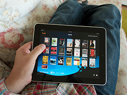 Man browsing digital e-book library on Amazon kindle app on an iPad touch screen tablet computer