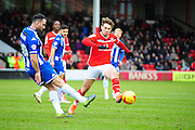 Craig Morgan of Wigan Athletic clears under pressure from  Tom Bradshaw of Walsall FC during the Sky Bet League 1 match between Walsall and Wigan Athletic at the Banks's Stadium, Walsall, England on 20 February 2016. Photo by Mike Sheridan.