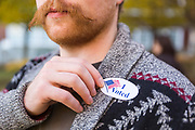 "Shelburne resident Charlie Laud leaves his local polling location with an ""I Voted"" sticker on Tuesday morning. Photographer in Burlington VT, Oliver Parini Photography."
