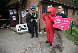 © Licensed to London News Pictures. 08/06/2017. Sonning, UK. Campaigner for father's rights Bobby Smith stands with an Elmo character before Prime Minister Theresa May and her husband Philip arrive at their local polling station to cast their vote in the general election. Polling stations are open from 7am - 10pm.  Photo credit: Peter Macdiarmid/LNP