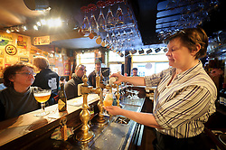 "Daisy Claeys, the owner of 't Brugs Beertje, in Bruges, Belgium, serves her customers. The 't Brugs Beertje is considered by many beer aficionados as one of the best beer houses in Europe. ""If you are European, you cannot call yourself a well-travelled beer lover unless you have drunk at Daisy's,"" writes British beer journalist Tim Webb in his essential traveler's tome, The Good Beer Guide to Belgium  (Kemelstraat 5 ; 32-50-33-96-16 ; brugsbeertje.be ). (Photo © Jock Fistick )"