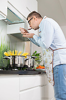 Mid-adult man tasting food while cooking in kitchen