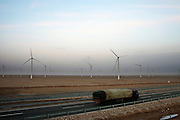 Gansu, China - 26 Feb 2010. A truck drives pass Guazhou wind farm near Yumen, Gansu province, China. China has set a target for renewable energy consumption of 40 percent of the market by the year 2050.Photographer: Markel Rendondo/Greenpeace.