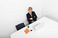 Portrait of confident businessman sitting at desk with laptop