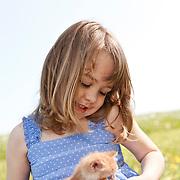Girl 4-6 years in sundress smiling at kitten in her lap vertical