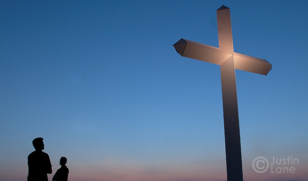 Two men are seen looking at the 190-ft cross located along Interstate-40 in Groom, TX Friday, July 15, 2005 . The cross is supposedly the largest in the western hemisphere.