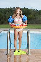 Portrait of girl (5-6) by pool with inflatable ring and swim fins