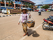 16 JUNE 2016 - PAKSE, CHAMPASAK, LAOS:  A woman sells dried fish from a basket she carries over her shoulder in Pakse. Pakse is the capital of Champasak province in southern Laos. It sits at the confluence of the Xe Don and Mekong Rivers. It's the gateway city to 4,000 Islands, near the border of Cambodia and the coffee growing highlands of southern Laos.     PHOTO BY JACK KURTZ