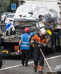 © Licensed to London News Pictures. 26/08/2017. Milton Keynes, UK. Part of the remains of the minibus on a recovery vehicle. The scene on the M1 motorway near Milton Keynes after a crash involving a minibus and two lorries. Police say that several people are dead and four others have been taken to hospital after the accident on the southbound carriageway in the early hours of this morning. Photo credit: Ben Cawthra/LNP