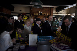 "© London News Pictures. ""Looking for Nigel"". A body of work by photographer Mary Turner, studying UKIP leader Nigel Farage and his followers throughout the 2015 election campaign. PICTURE SHOWS - UKIP voters queue up to have their window posters and campaign materials signed after a hearing Nigel Farage speak at a public meeting in The Holly Tree pub in Margate, Kent, on April 18th 2015. Mr Farage spoke at nearly 30 public meetings that took place in village halls, pubs, community and leisure centres around the country in his bid to be elected at MP in Thanet. . Photo credit: Mary Turner/LNP **PLEASE CALL TO ARRANGE FEE** **More images available on request**"
