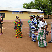 "Pognamine (plural of ""pognaa"", or woman chief) have their photograph taken on a cellphone as they wait for a van to pick them up in Lawra in the Upper West region of Ghana on 25 June 2015. A pognaa is responsible, in particular, for the wellbeing of women and children in her area of authority. While the title translates as ""woman chief"", in practice her authority is  subject to a male chief. The role of the pognamine is being revived after having been suppressed during the colonial era, and they are increasingly seen as a force for development."