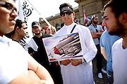 Mainz | 18 July 2014<br /> <br /> Am Samstag (18.07.2014) nahmen etwa 1000 M&auml;nner, Frauen und Kinder in der Innenstadt von Mainz anl&auml;sslich der milit&auml;rischen Auseinandersetzung zwischen Israel und der Hamas in Gaza an einer Solidarit&auml;tsdemonstration f&uuml;r Gaza, ein freies Pal&auml;stina und gegen Israel teil. Bei der Demo wurden Fahnen der Hamas und der Hisbollah mitgef&uuml;hrt, neben den &uuml;blichen Parolen gegen Israel wurde in Sprechch&ouml;hren auch vereinzelt zur Vernichtung von J&uuml;dinnen und Juden aufgerufen.<br /> Hier: Ein junger Mann mit Djihadisten-Stirnband h&auml;lt eine Karikatur, die ein pal&auml;stinensisches Kind mit Papierflieger zeigt, das von einem mit Bomben und Raketen aufger&uuml;steten israelischen Kampfflugzeug bedroht wird.<br /> <br /> <br /> &copy;peter-juelich.com<br /> <br /> [No Model Release | No Property Release]