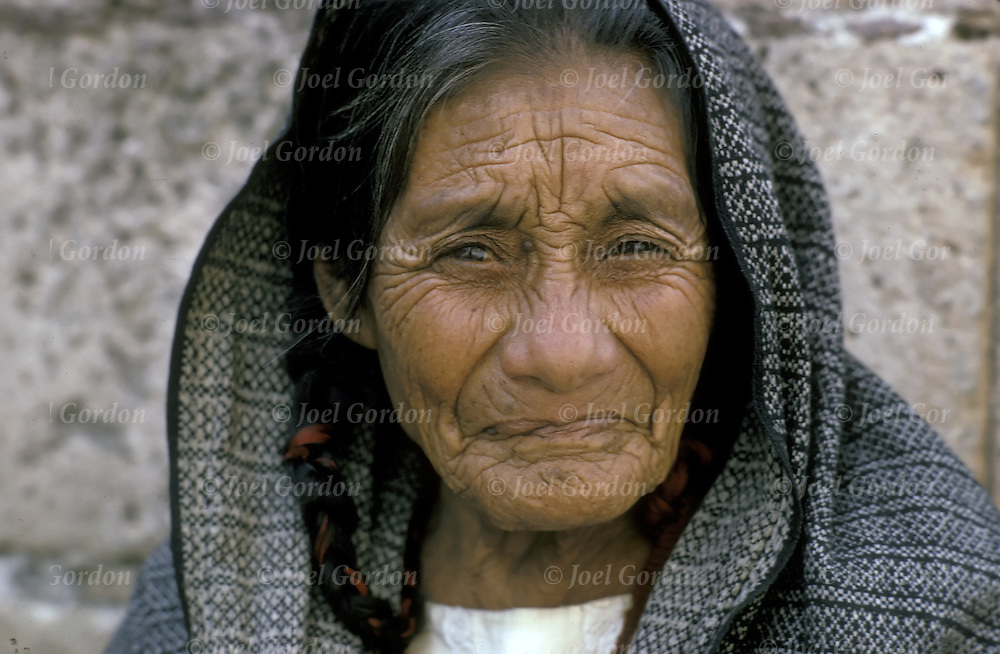Wrinkled as a prunes elderly Mexican woman looking directly at camera. What is beauty?